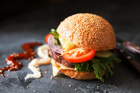 Homemade hamburger with fresh vegetables and melted cheese close up