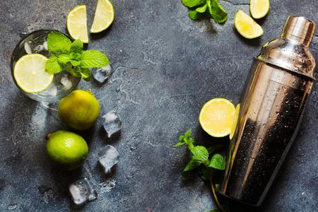 Ingrediënten voor het maken van mojito zomer cocktail, limoen, munt en bar tools van bovenaf op donkere leisteen achtergrond