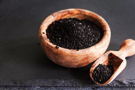 黒いスレートの背景にスプーンとボウルの黒クミンまたはニゲラサティバまたはカロンジ種子、選択的な焦点 写真素材