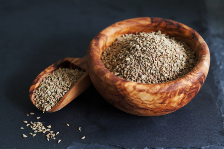 Closeup of ajwain seeds in a wooden bowl over darl slate background with copy space
