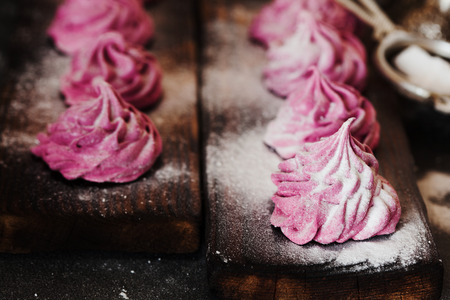 Close up of pink homemade zephyr or marshmallow in powdered sugar on dark background. Marshmallow, Meringue, Zephyr