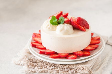 Light cheesecake with strawberry filling decorated with fresh berries and mint. Healthy organic summer dessert pie.
