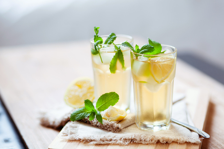 Refreshing summer drink with lemon, mint and ice. Glasses with cold and healthy beverage, place for text