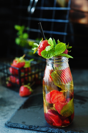 Strawberry lemonade drink, refreshing summer lemonade with fresh berries and mint on dark background
