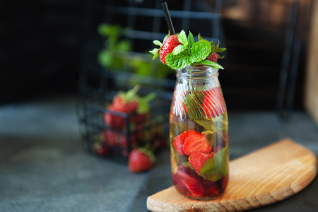 Strawberry lemonade drink, refreshing summer lemonade with fresh berries and mint on dark background, copy space