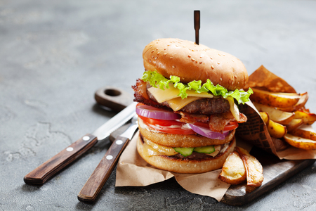 Tasty lunch with grilled beef burger with bacon and french fries served on a rustic wooden board on dark slate background