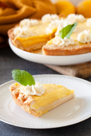 Piece of traditional shortcrust pastry lemon tart with citrus custard and decorated with whipped cream