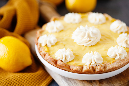 Traditional shortcrust pastry lemon tart with citrus custard and decorated with whipped cream
