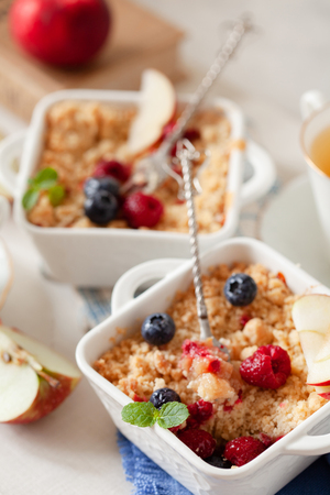 Traditional British apple crumble on portion baking dish with fresh berries close up Stock Photo