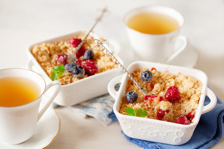 Traditional British apple crumble on portion baking dish with fresh berries close up Banque d'images