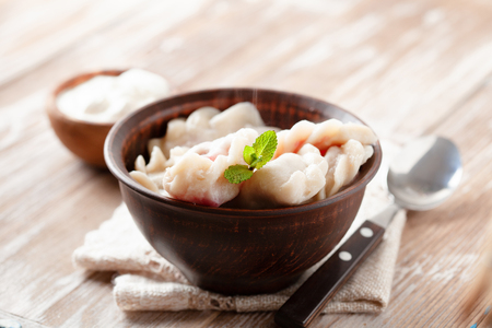 Dumplings, filled with cherry and sour cream on wooden table. Pierogi, varenyky, vareniki - dumplings with filling, popular dish in many countries
