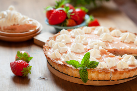Strawberry tart cake decorated with whipped cream. Summer dessert pie with fresh berries on wooden table