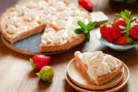Slice of strawberry tart cake decorated with whipped cream. Summer dessert pie with fresh berries on wooden table