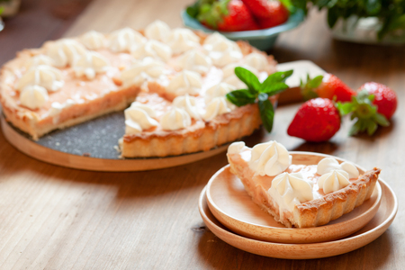 Slice of strawberry tart cake decorated with whipped cream. Summer dessert pie with fresh berries on wooden table Stockfoto - 116130687
