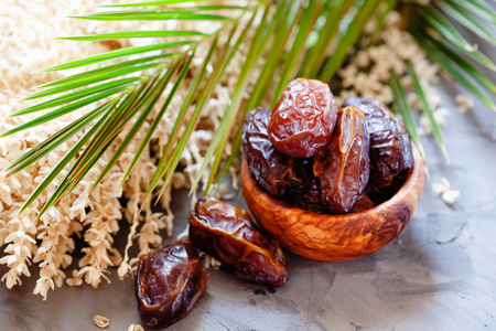 Assiette de dattes medjool bio crues avec feuilles et fleurs de palmier dattier