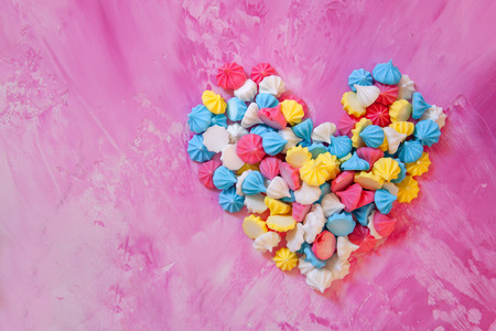 Pastel colored merengues cookies in heart shape on pink background top view