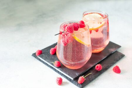 Sparkling pink raspberry lemonade on grey background  copy space