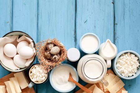Diversi tipi di prodotti lattiero-caseari su fondo di legno blu: latte, panna acida, ricotta, formaggio, panna, yogurt, uova e burro. Vista dall'alto con copia spazio