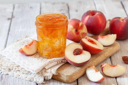 Süße hausgemachte natürliche Pfirsichmarmelade auf dem Holztisch Standard-Bild