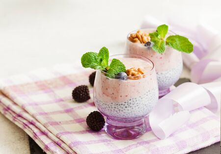 Layered chia and berry smoothie in purple glass, healthy food style with copy space
