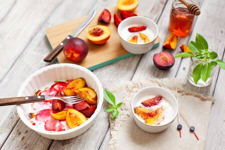 Greek yogurt with grilled fruits and honey. Easy healthy sweet summer dessert with plum and peach