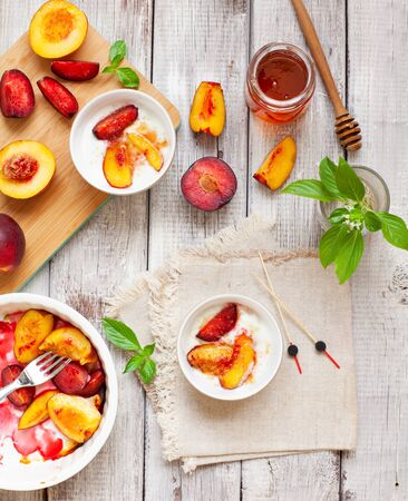 Greek yogurt with grilled fruits and honey. Easy healthy sweet summer dessert with plum and peach top view