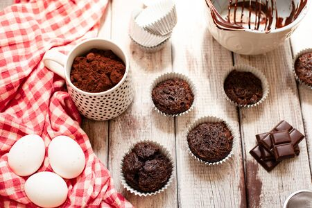 Ð¡hocolate muffins with colorful pastry topping on a wooden table with ingredients, cooking process Stockfoto - 128883732