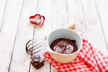 Melted chocolate in ceramic bowl on wooden background copy space, cooking process  Stockfoto