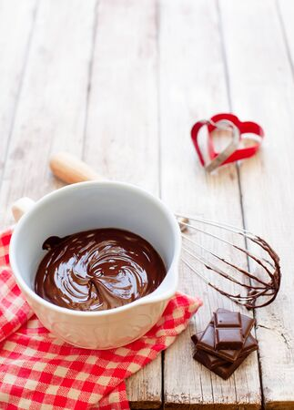 Melted chocolate in ceramic bowl on wooden background copy space, cooking process Stockfoto - 128883736