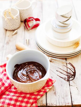 Melted chocolate in ceramic bowl on wooden background copy space, cooking process Stockfoto - 128883734