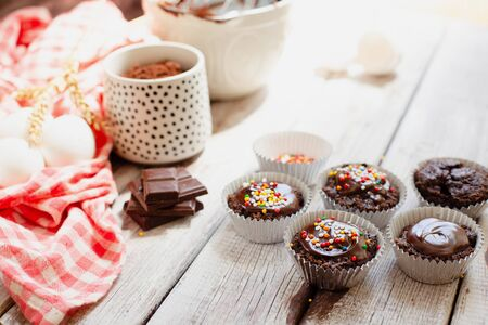 Ð¡hocolate muffins with colorful pastry topping on a wooden table with ingredients, cooking process Stockfoto - 128883739