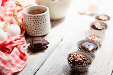 Ð¡hocolate muffins with colorful pastry topping on a wooden table with ingredients, cooking process