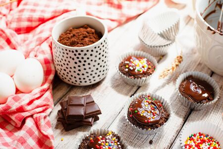Ð¡hocolate muffins with colorful pastry topping on a wooden table with ingredients, cooking process Stockfoto - 128883749