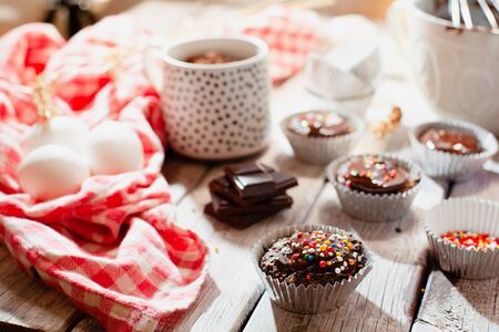 Ð¡hocolate muffins with colorful pastry topping on a wooden table with ingredients, cooking process Stockfoto - 128883747