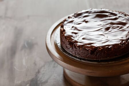 Chocolate brownie cake with ganashe topping on gray background, closeup