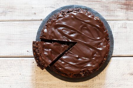 Chocolate brownie cake with ganashe topping on wooden background top view