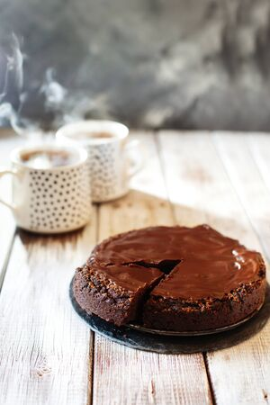 Chocolate brownie cake with ganashe topping and two cups of hot tea on wooden background top view