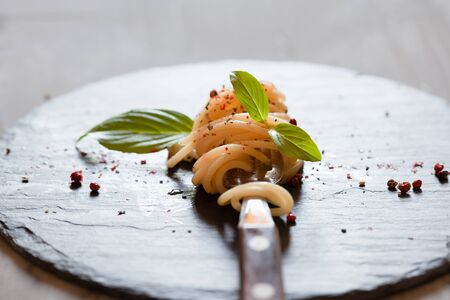 Fork with classic italian spaghetti pasta with basil and cheese on dark slate board