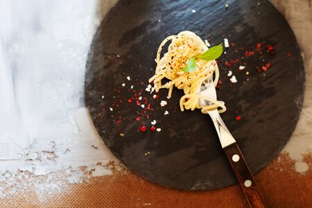 Fork with classic italian spaghetti pasta with basil and cheese on dark slate board top view