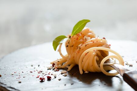Fork with classic italian spaghetti pasta with basil and cheese on dark slate board Stockfoto - 129093500