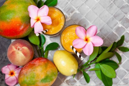 Fresh tropical fruit smoothie mango juice with leaves and fruits top view