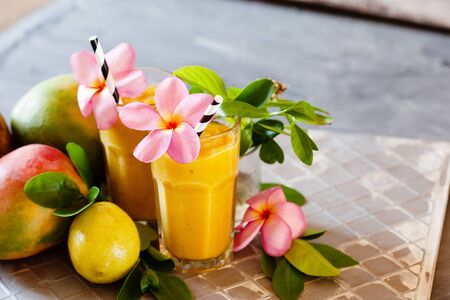 Fresh tropical fruit smoothie mango juice with leaves and fruits Stockfoto - 129161720