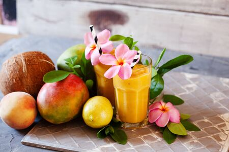 Fresh tropical fruit smoothie mango juice with leaves and fruits Stockfoto - 129161719