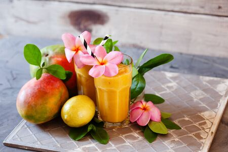 Fresh tropical fruit smoothie mango juice with leaves and fruits