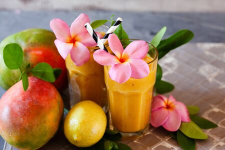 Fresh tropical fruit smoothie mango juice with leaves and fruits Stockfoto - 129161722