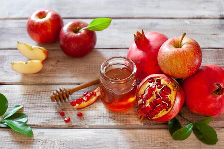 Rosh Hashana concept, jewish New Year holiday with traditional symbols: apples, pomegranate and honey top view