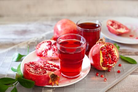Pomegranate juice with fresh pomegranate fruits on wooden table. Healthy vitamin drink concept to raise hemoglobin close up Stockfoto