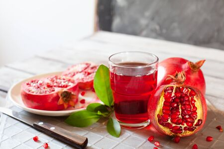 Pomegranate juice with fresh pomegranate fruits on wooden table. Healthy vitamin drink concept to raise hemoglobin close up Stockfoto - 129256778