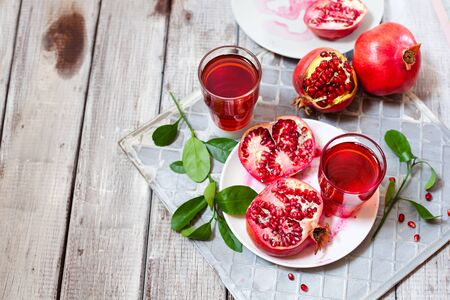Pomegranate juice with fresh pomegranate fruits on wooden table. Healthy vitamin drink concept to raise hemoglobin top view Stockfoto