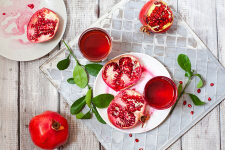 Pomegranate juice with fresh pomegranate fruits on wooden table. Healthy vitamin drink concept to raise hemoglobin top view Stockfoto - 129256787